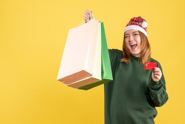 Vue de face jeune femme avec carte bancaire et forfaits shopping