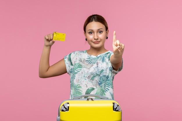 Vue de face d'une jeune femme avec une carte bancaire jaune et un sac sur le mur rose