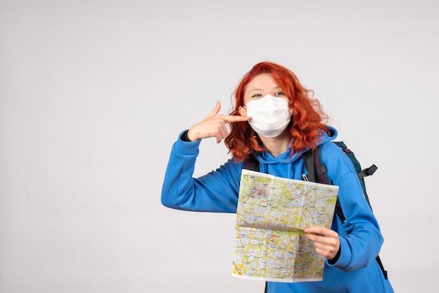 Vue de face de la jeune femme avec carte en masque sur mur blanc