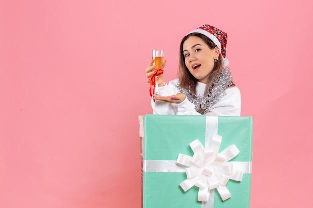 Vue de face de la jeune femme célébrant noël avec un verre sur le mur rose