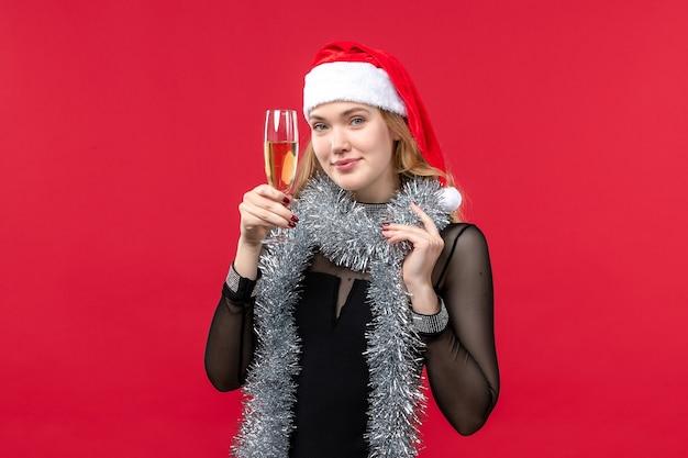 Vue de face jeune femme célébrant le nouvel an avec du champagne sur la couleur de noël de mur rouge