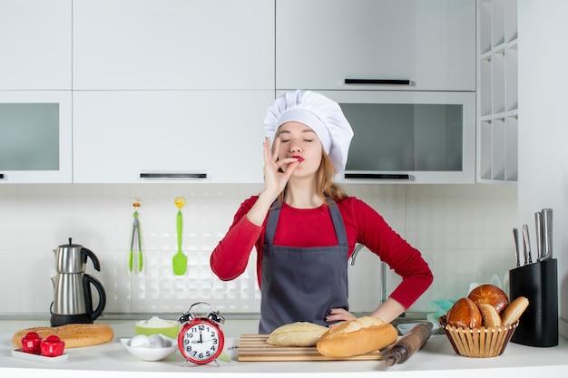 Vue de face jeune femme en chapeau de cuisinier et tablier faisant un baiser en chef dans la cuisine
