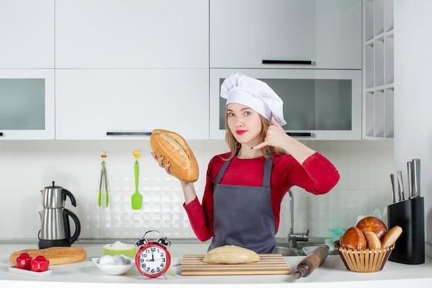 Vue de face jeune femme en chapeau de cuisinier et tablier faisant signe okey tenant du pain dans la cuisine