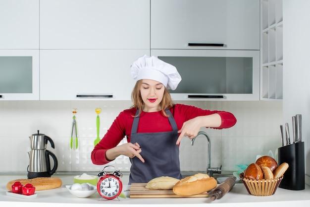Vue de face jeune femme en chapeau de cuisinier et tablier pointant sur du pain sur planche de bois dans la cuisine