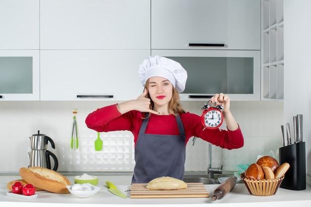 Vue de face jeune femme en chapeau de cuisinier et tablier tenant un réveil rouge me faisant signe dans la cuisine