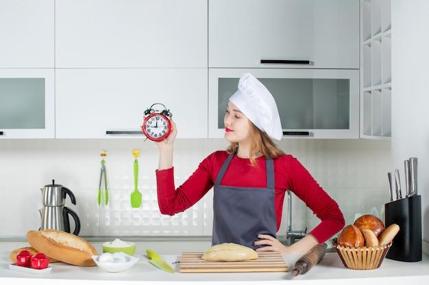 Vue de face jeune femme en chapeau de cuisinier et tablier tenant un réveil rouge mettant la main sur une taille dans la cuisine