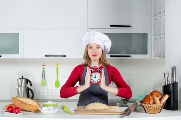 Vue de face jeune femme en chapeau de cuisinier tenant un réveil rouge dans la cuisine
