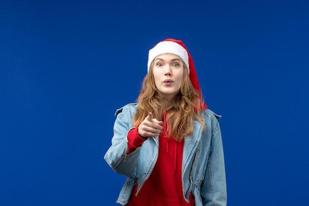 Vue de face jeune femme avec chapeau de noël rouge sur le bureau bleu vacances d'émotion de noël