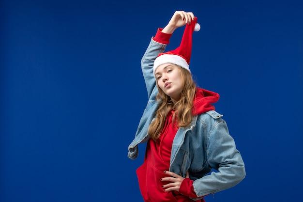 Vue de face jeune femme avec chapeau de noël rouge sur fond bleu couleur de noël émotions