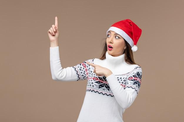 Vue de face jeune femme avec chapeau de noël rouge sur fond marron émotions de noël nouvel an