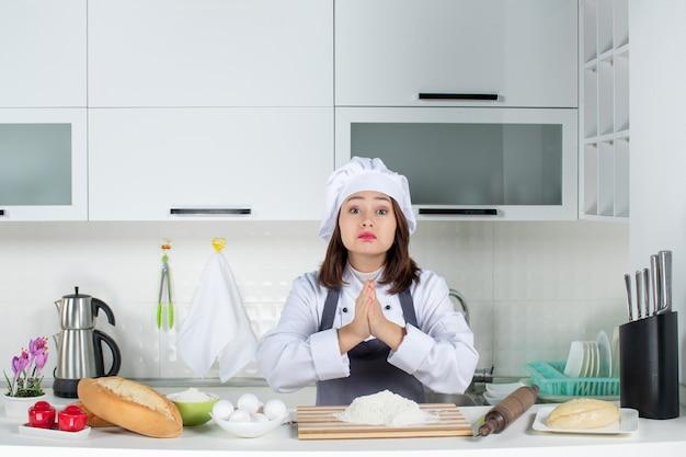 Vue de face d'une jeune femme chef en uniforme priant pour quelque chose dans la cuisine blanche