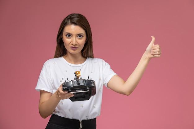 Vue de face jeune femme en chemise blanche à l'aide de la télécommande sur le mur rose, modèle femme couleur posant femme