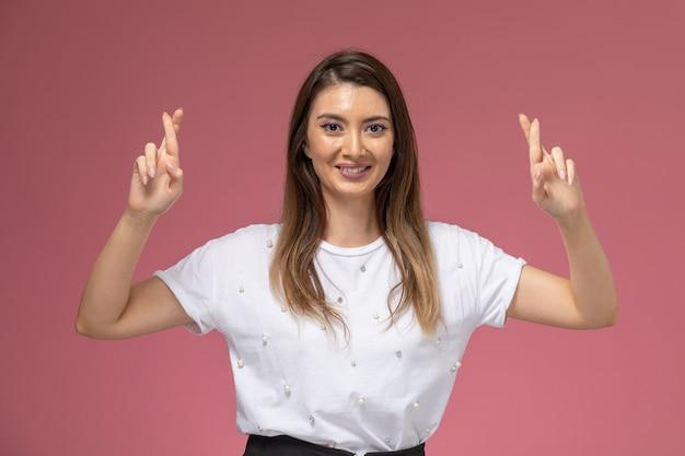 Vue de face jeune femme en chemise blanche montrant les doigts croisés souriant sur mur rose, femme modèle femme couleur