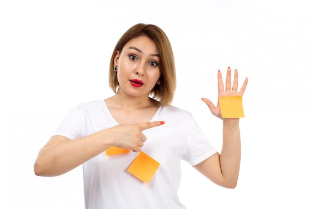 Une vue de face jeune femme en chemise blanche avec des notes orange posant montrant une note orange sur le blanc