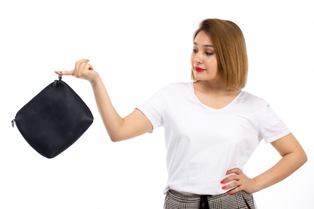 Une vue de face jeune femme en chemise blanche et pantalon moderne léger tenant un petit sac noir sur le blanc