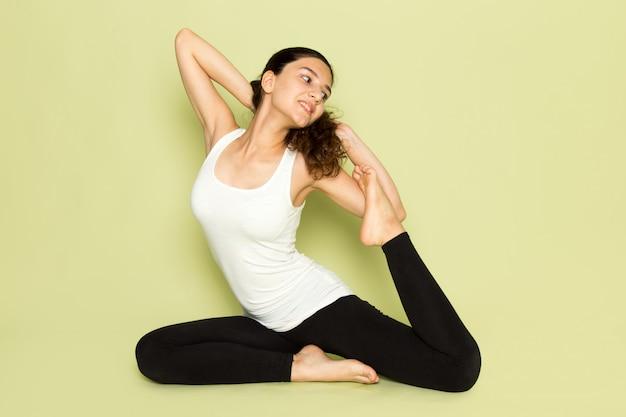 Une vue de face jeune femme en chemise blanche et pantalon noir posant assis en posture de yoga