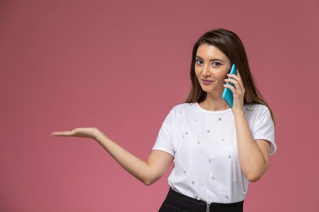 Vue de face jeune femme en chemise blanche, parler au téléphone sur le mur rose