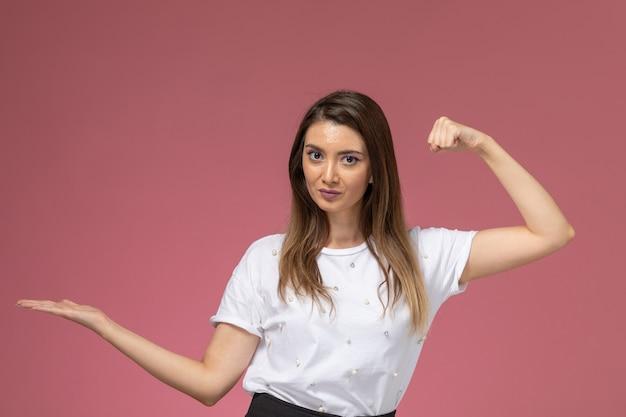 Vue de face jeune femme en chemise blanche posant avec la main levée et fléchissant sur le mur rose, modèle femme couleur posant femme