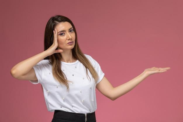 Vue de face jeune femme en chemise blanche posant avec la main levée sur le mur rose, modèle femme couleur posant femme
