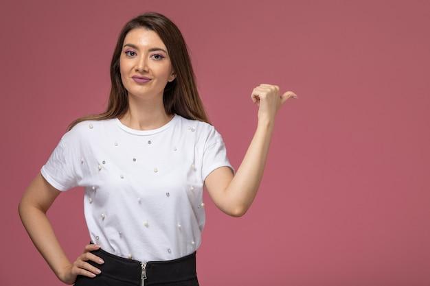 Vue de face jeune femme en chemise blanche posant et soulignant sur le mur rose, modèle femme pose