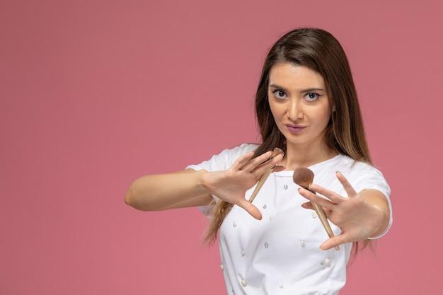 Vue de face jeune femme en chemise blanche posant et tenant un pinceau de maquillage sur le mur rose, modèle femme
