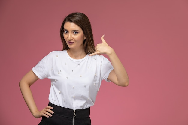 Vue de face jeune femme en chemise blanche souriant posant sur un mur rose, modèle de pose de femme de couleur