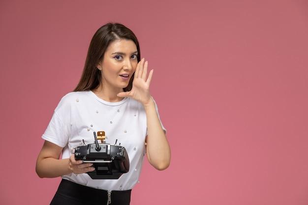 Vue de face jeune femme en chemise blanche tenant la télécommande chuchotant