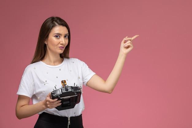 Vue de face jeune femme en chemise blanche tenant la télécommande sur le mur rose, modèle de couleur femme pose