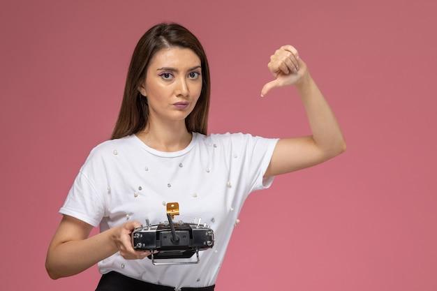 Vue de face jeune femme en chemise blanche tenant la télécommande sur le mur rose, modèle de couleur femme