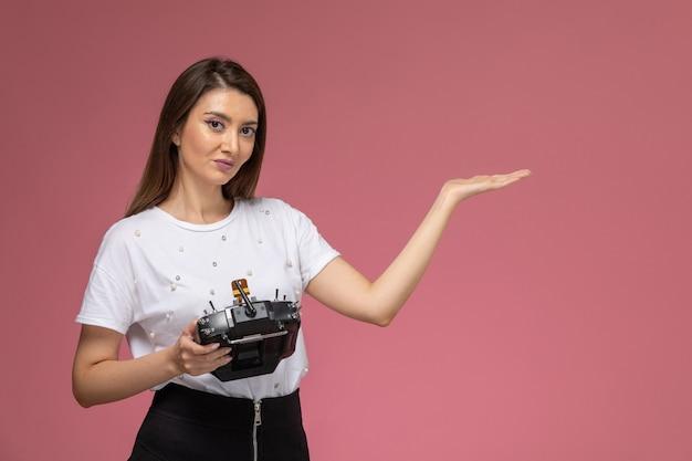 Vue de face jeune femme en chemise blanche tenant la télécommande sur le mur rose, modèle femme