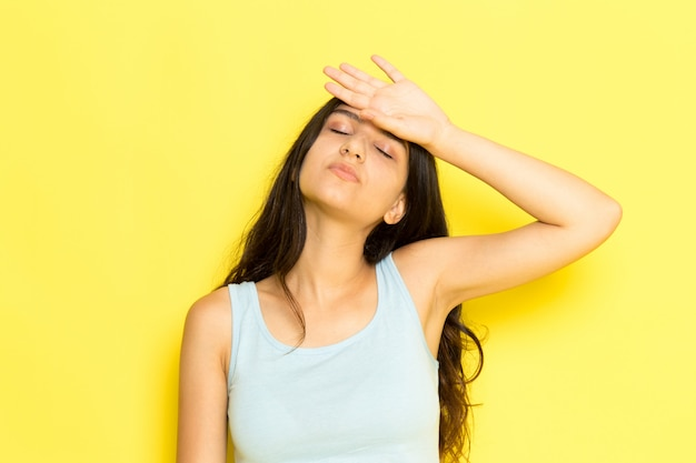 Une vue de face jeune femme en chemise bleue ayant une température sévère touchant son front