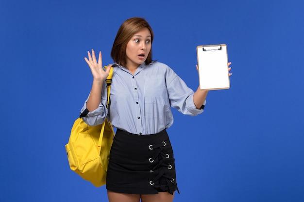 Vue de face de la jeune femme en chemise bleue jupe noire portant un sac à dos jaune tenant le bloc-notes sur le mur bleu clair
