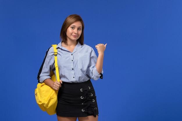 Vue de face de la jeune femme en chemise bleue portant un sac à dos jaune posant et souriant sur le mur bleu