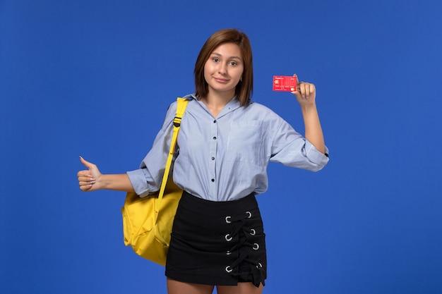 Vue de face de la jeune femme en chemise bleue portant un sac à dos jaune tenant une carte en plastique rouge sur le mur bleu