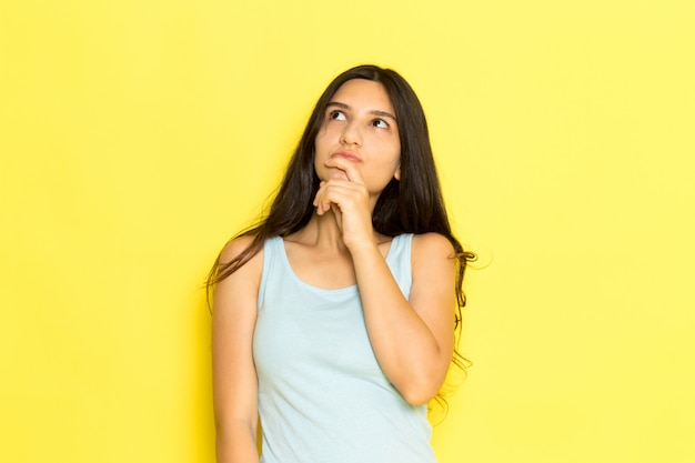 Une vue de face jeune femme en chemise bleue posant avec expression de pensée