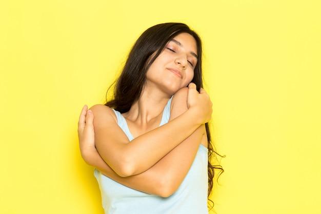 Une vue de face jeune femme en chemise bleue posant et se serrant dans ses bras
