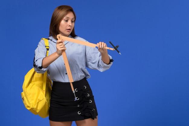 Vue de face de la jeune femme en chemise bleue tenant la forme de triangle en bois