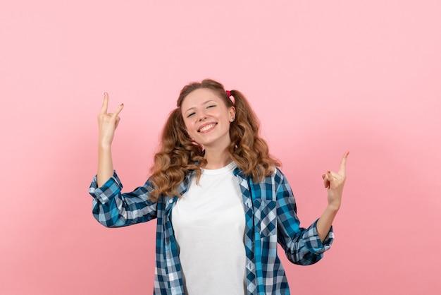 Vue de face jeune femme en chemise à carreaux posant sur fond rose clair jeune femme couleur émotions modèle kid