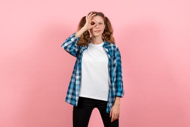 Vue de face jeune femme en chemise à carreaux posant sur fond rose clair jeune femme émotions modèle couleur enfant