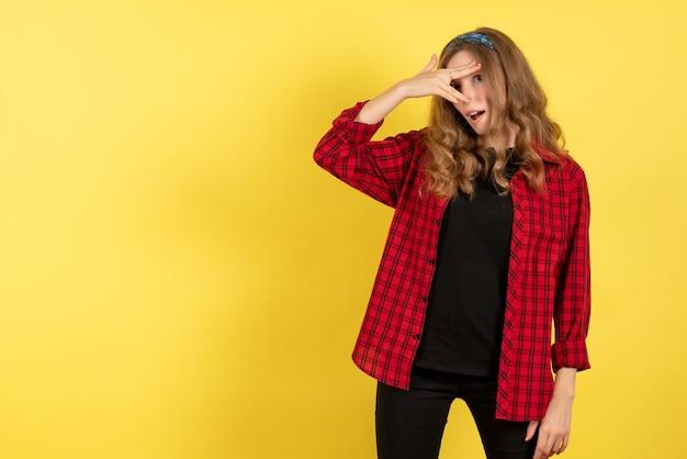 Vue de face jeune femme en chemise à carreaux rouge juste debout et posant sur fond jaune modèle fille femme couleur émotions humaines
