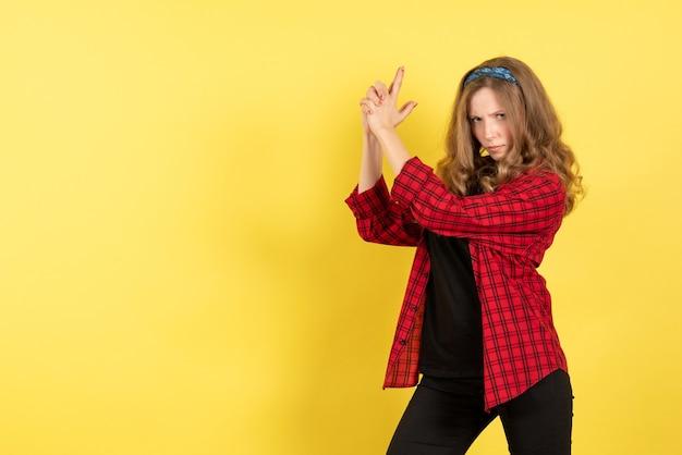 Vue de face jeune femme en chemise à carreaux rouge posant sur bureau jaune filles femme émotions modèle couleur humaine