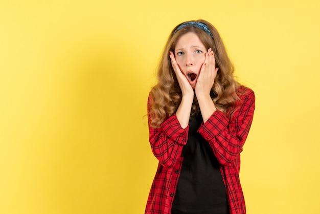 Vue de face jeune femme en chemise à carreaux rouge posant sur fond jaune filles émotions couleur modèle humain femme