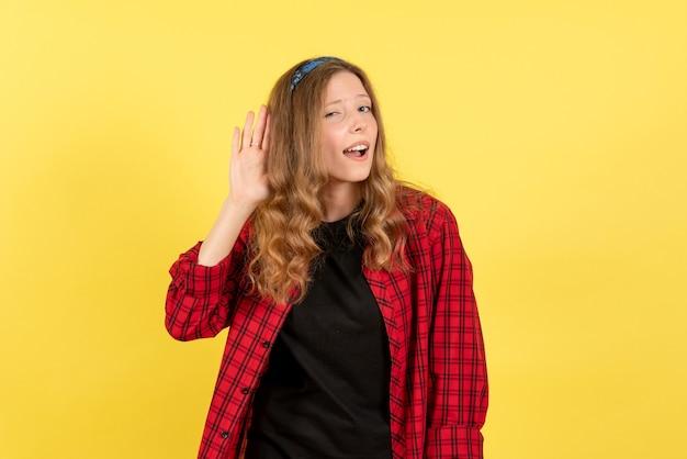 Vue de face jeune femme en chemise à carreaux rouge posant de manière à l'écoute sur fond jaune filles émotions couleur modèle humain femme