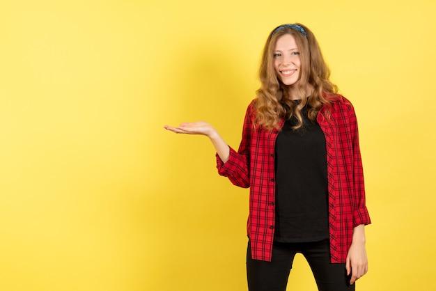 Vue de face jeune femme en chemise à carreaux rouge posant et montrant ses émotions sur fond jaune femme émotion humaine modèle fashion girl