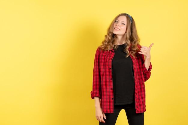 Vue de face jeune femme en chemise à carreaux rouge posant avec sourire sur fond jaune clair modèle d'émotion femme couleur humaine