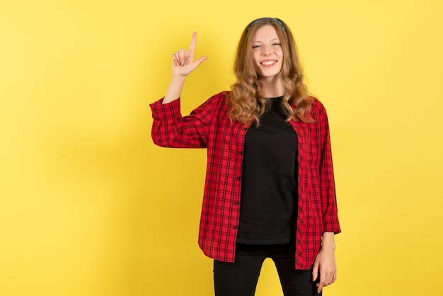 Vue de face jeune femme en chemise à carreaux rouge posant avec sourire sur fond jaune les émotions humaines modèle couleur femme