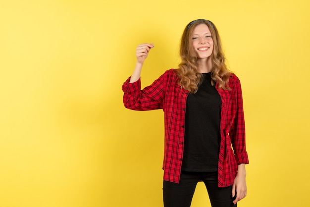 Vue de face jeune femme en chemise à carreaux rouge posant avec sourire sur fond jaune fille humaine émotions modèle couleur femme