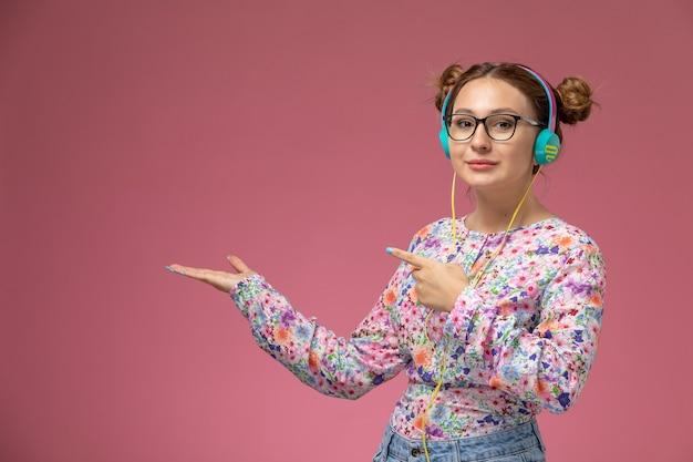 Vue de face jeune femme en chemise conçue de fleurs et blue-jeans, écouter de la musique avec un casque sur le bureau rose