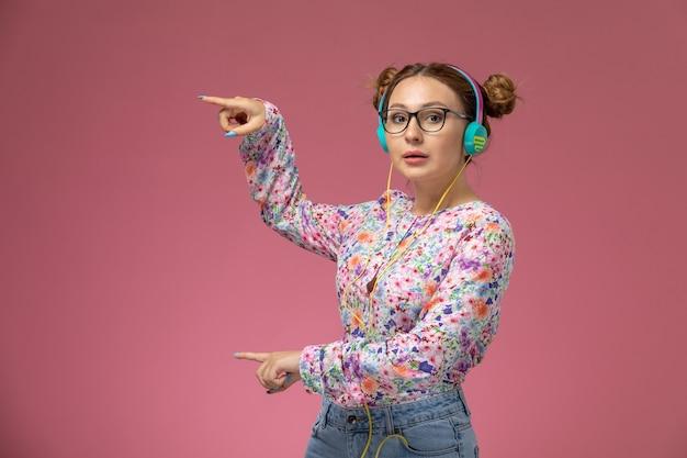Vue de face jeune femme en chemise conçue de fleurs et blue-jeans, écouter de la musique avec des écouteurs sur fond rose