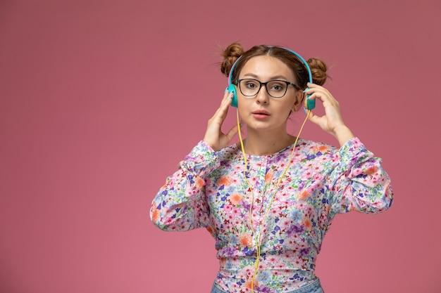 Vue de face jeune femme en chemise conçue de fleurs et blue-jeans, écouter de la musique avec des écouteurs sur le modèle de fond rose femme